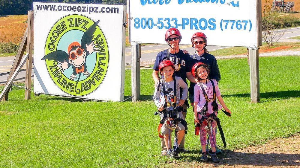 family of 4 in zipline harnesses standing in front of sign for Ocoee Zips