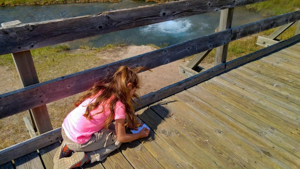 A little girl leaning on a bridge writing in her notebook while overlooking a stream for homeschool