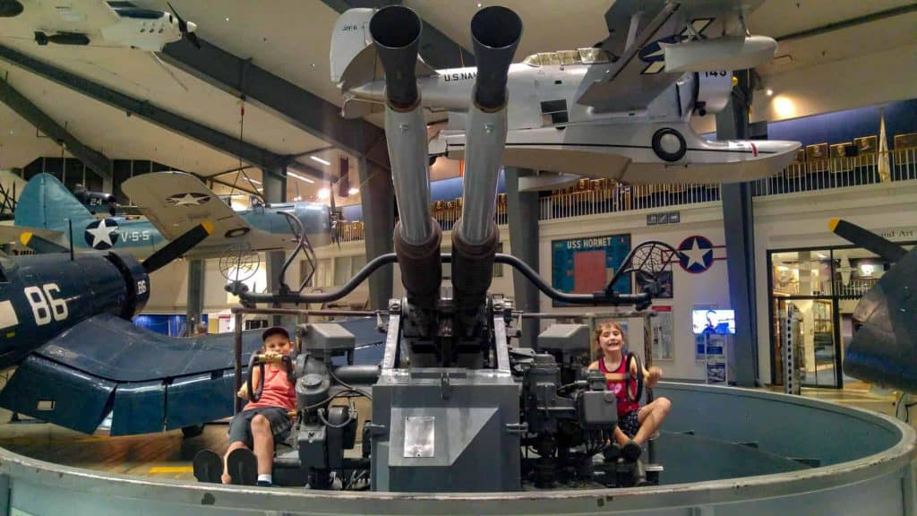 Two kids sitting on either side of a fighter gun for homeschool