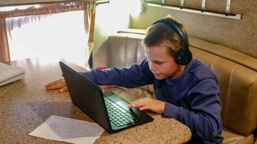 A young boy on his computer doing homeschool in an RV