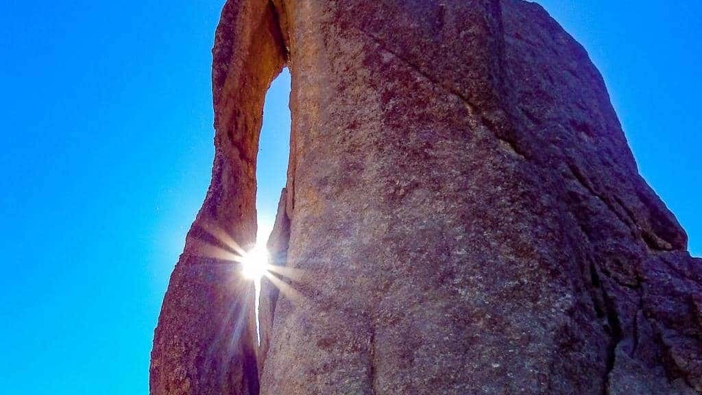 sun shining through the eye of the needle formation along needles highway in custer state park