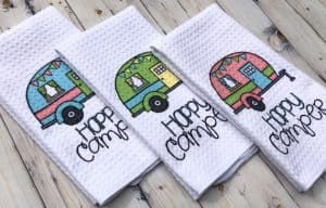 A cute set of three tea towels with happy camper and an old fashioned RV