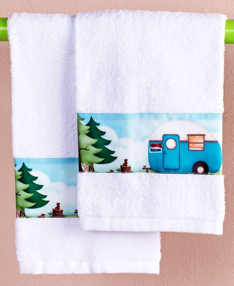 A matching set of RV camping hand towels with cute little rvs on it and a pretty green tree.