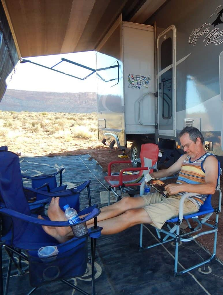 Frank sitting outside under our RV screen reading a book while RV boondocking