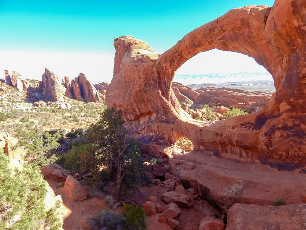 family sittung below double o arch at Arches national park