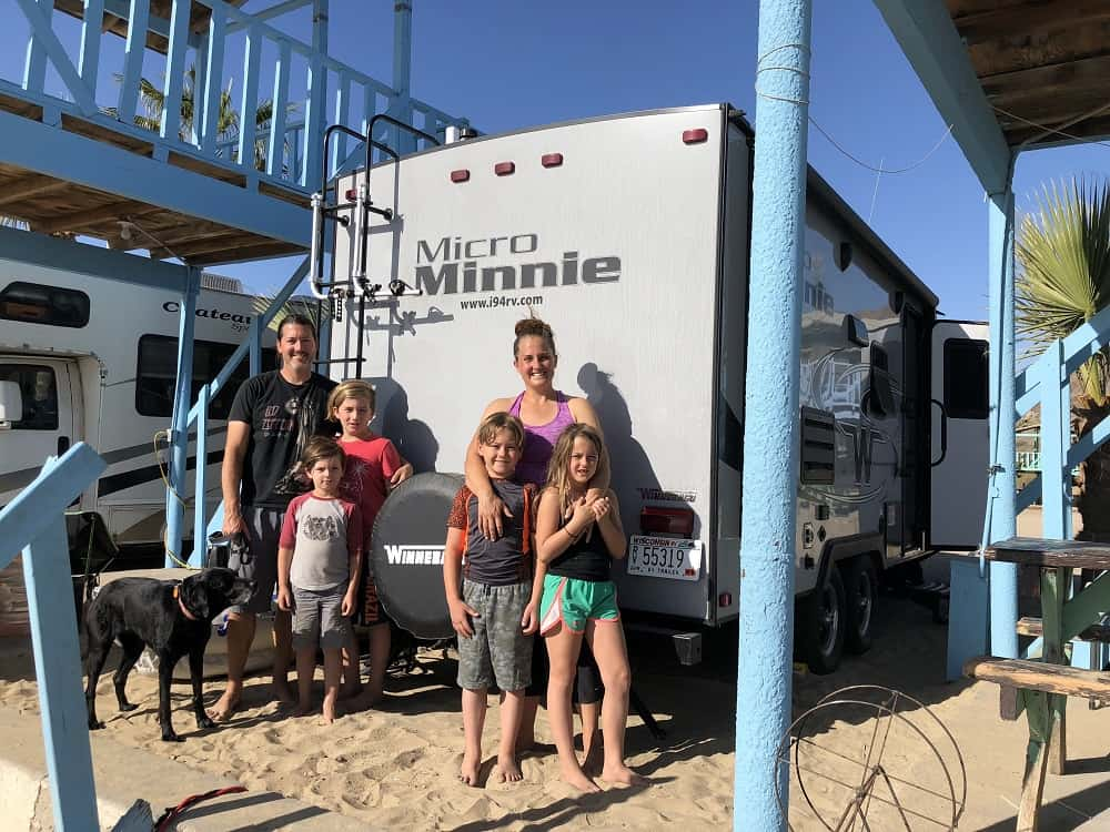 A family of 6 standing in front of their Miniie Micro RV on the beach