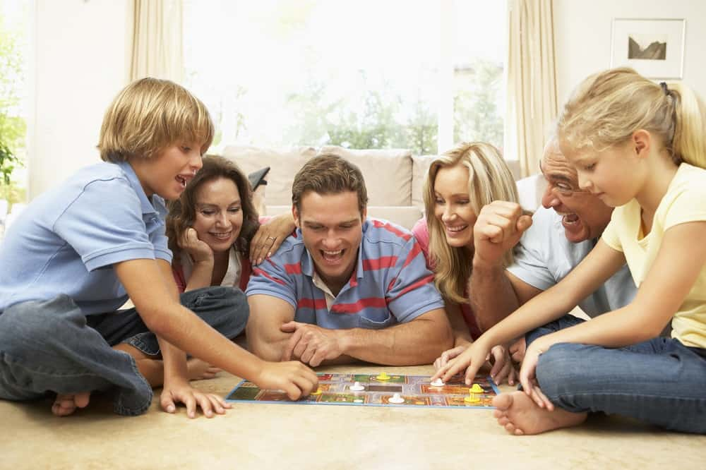 An entire family laying on the floor playing a board game