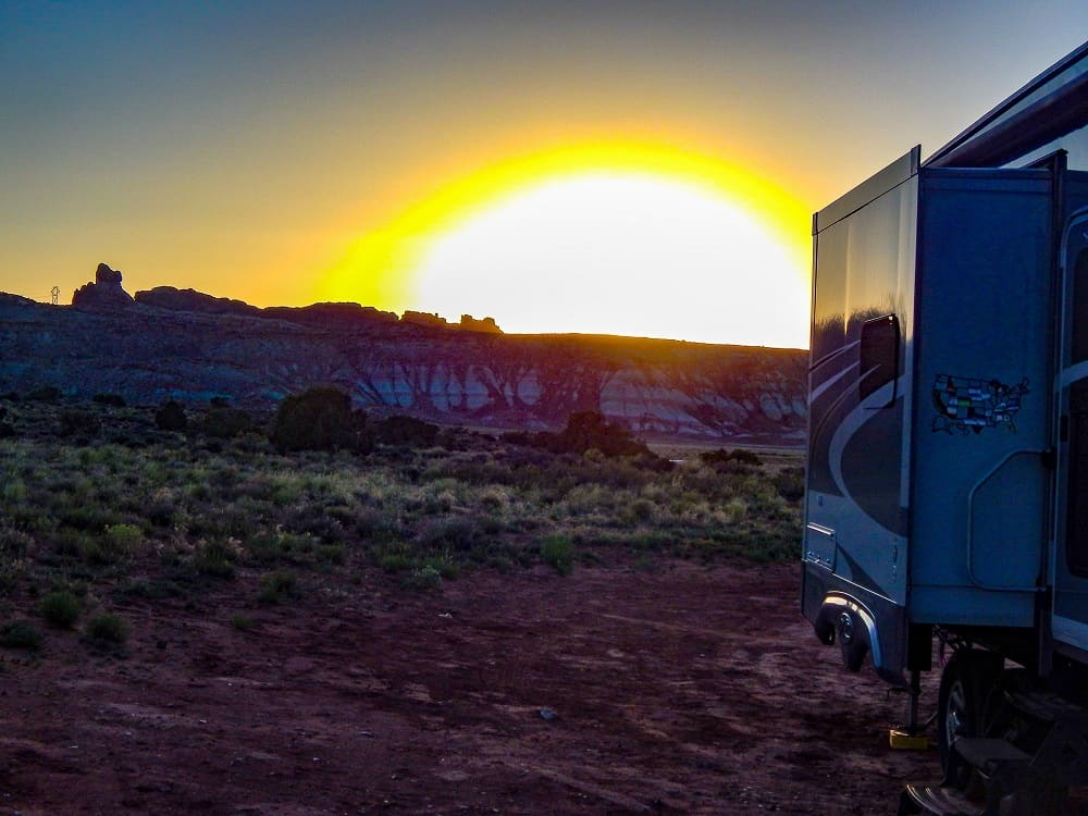 rv with sun setting over the buttes in the background near arches national park utah