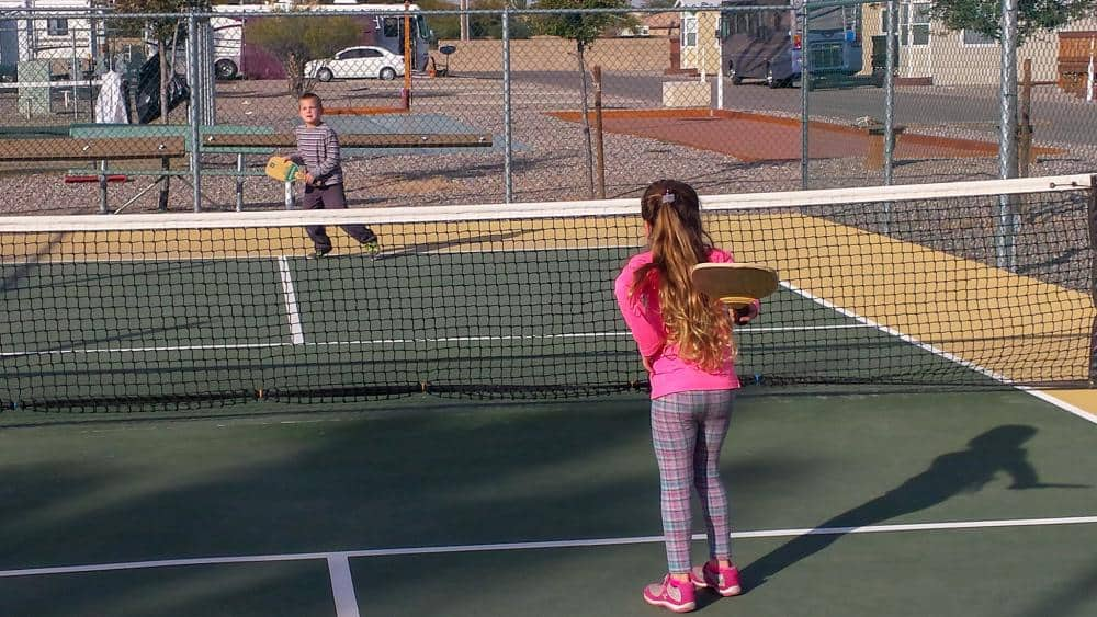 The kids having a blast playing pickle ball at the RV campground
