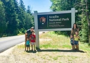 A family of 5 standing beside a National Park sign surrounded by lush, green trees in the background