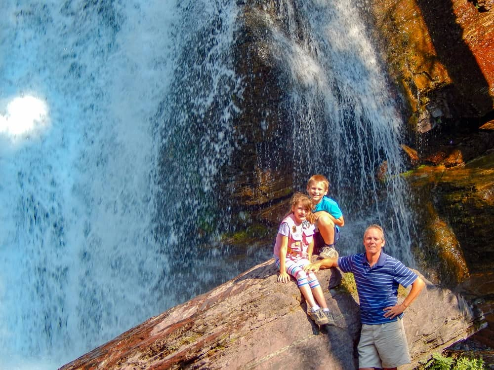Father and kids sitting on a giant rock in front of a waterfall.