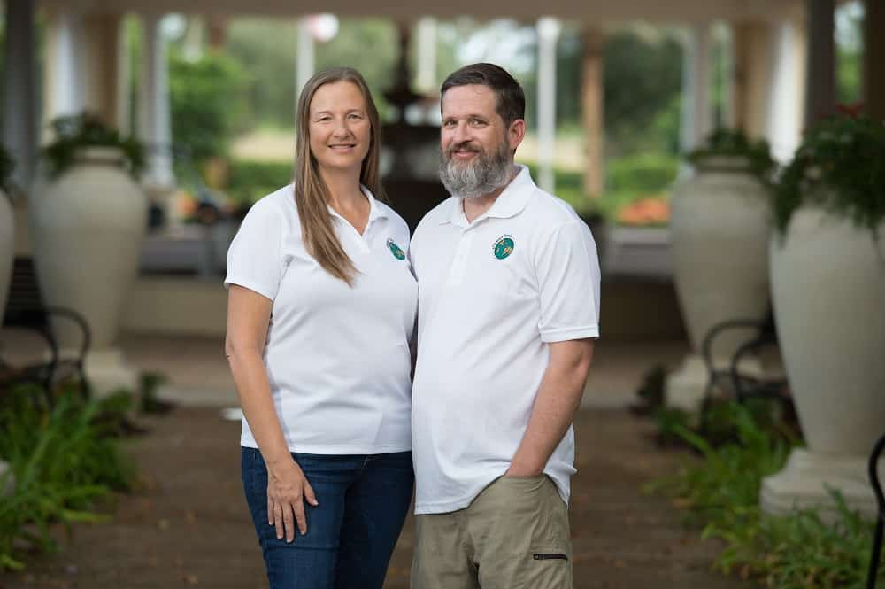 A man with a beard and a woman with long harir standing closely together in similar white tee shirts