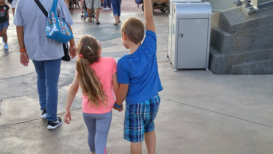 A girl in a pink tshirt and a boy in a blue tshirt holding hands together