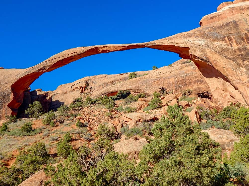 The rocks making an arch formation high up in the blue sky, with green shrubs on the ground