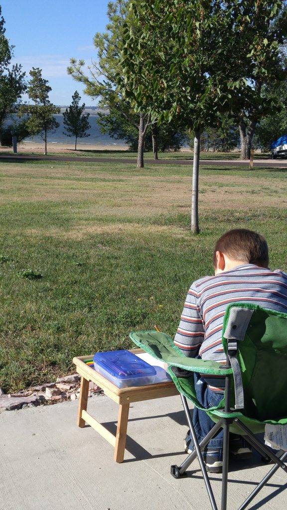 A boy sitting outside on a chair with a small table in front drawing a picture of the landscape