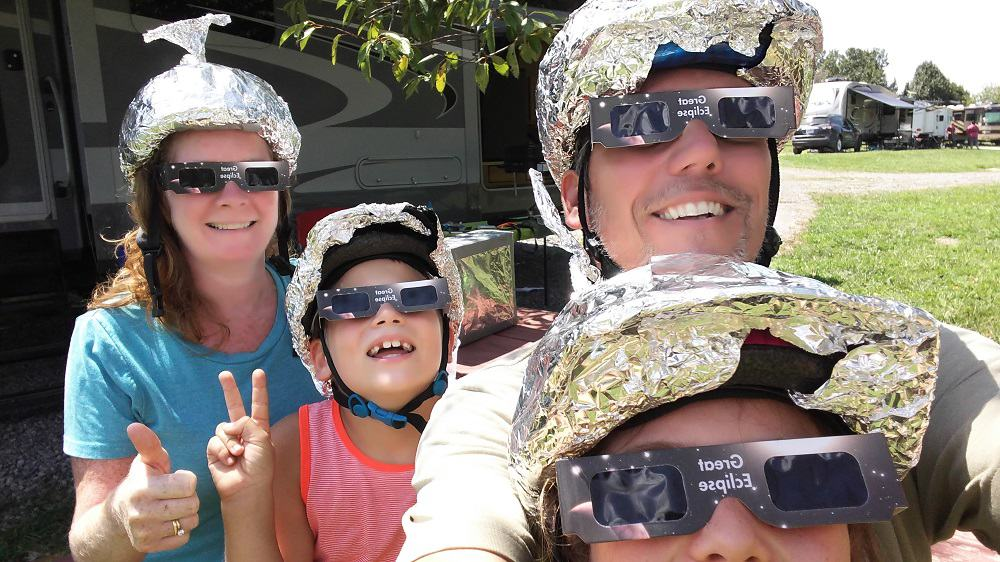 2 adults and 2 kids sitting together on chairs outside their RV with aluminum foil hats on their heads looking up at the blue sky