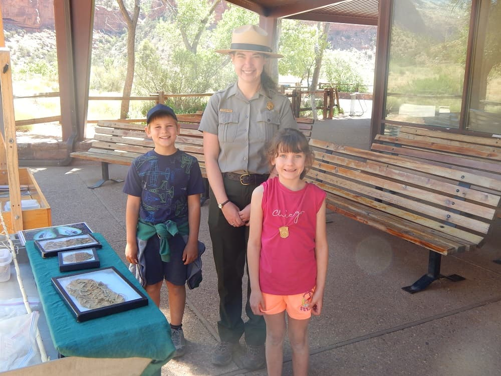 A boy and a girl with a park ranger surrounded by trees in the National Park area