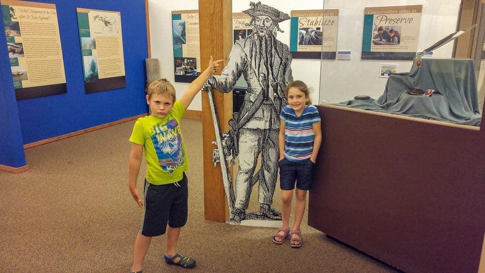 kids standing in front of Blackbeard cutout in okracoke