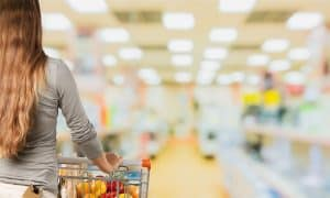 Lady shopping with her cart at a supermarket where she is hoping to save money on groceries