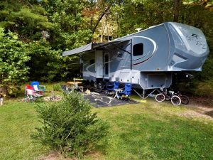 open range 5th wheel in wooded setting with camp fire and chairs