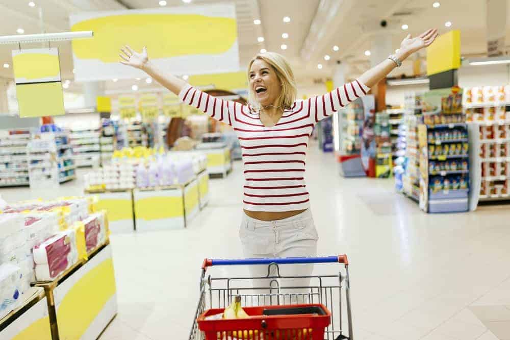 Woman jumping from joy in supermarket from happiness