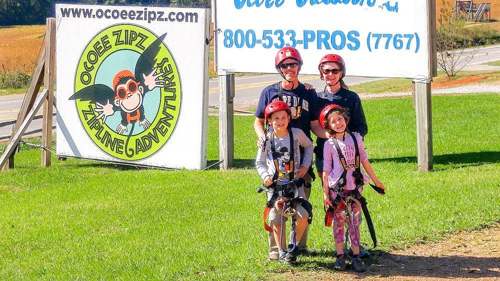 family of 4 in zipline harnesses standing in front of sign for Ocoee Zips