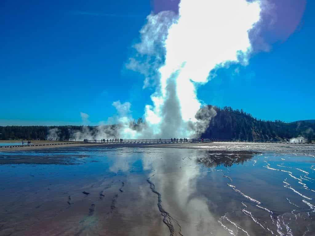 plume of steam from grand prismatic spring reflected in a pool of water below at yellowstone national park