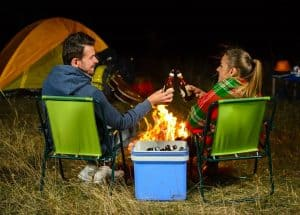 A couple enjoying an awesome Valentines Day sitting by a campfire enjoying a beer together