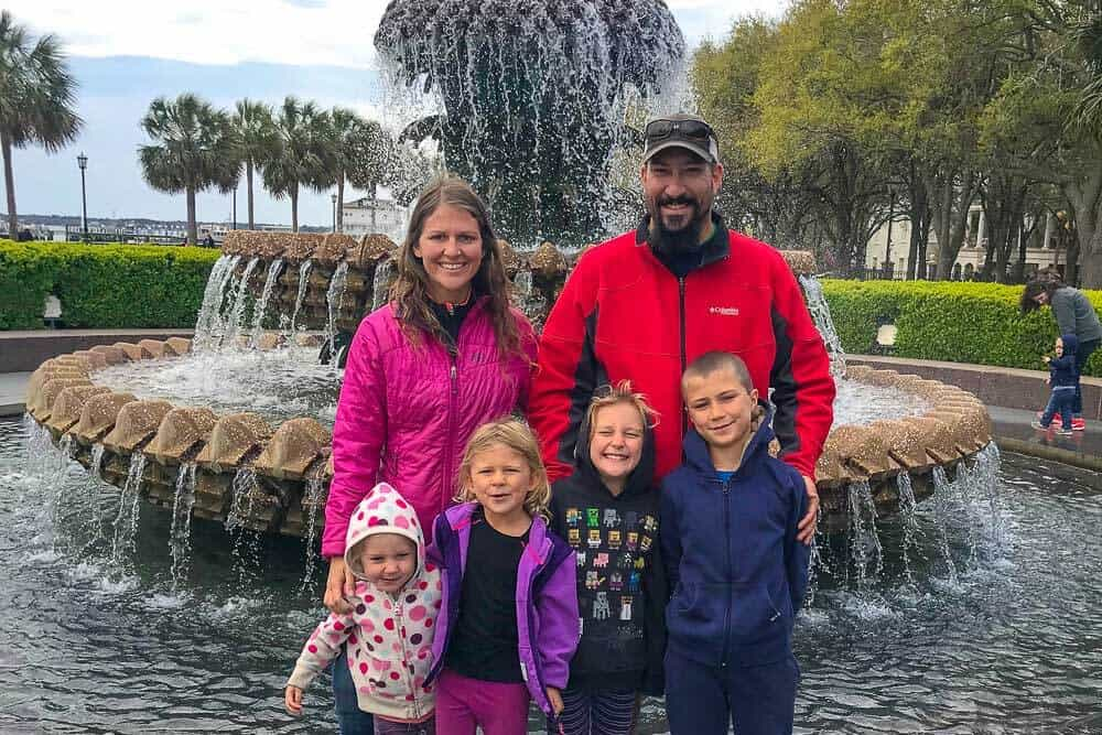 A man and woman standing in front of a waterfall with their 4 kids!