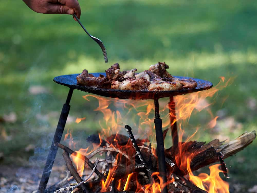 A person cooking outside on a campfire using camping essentials