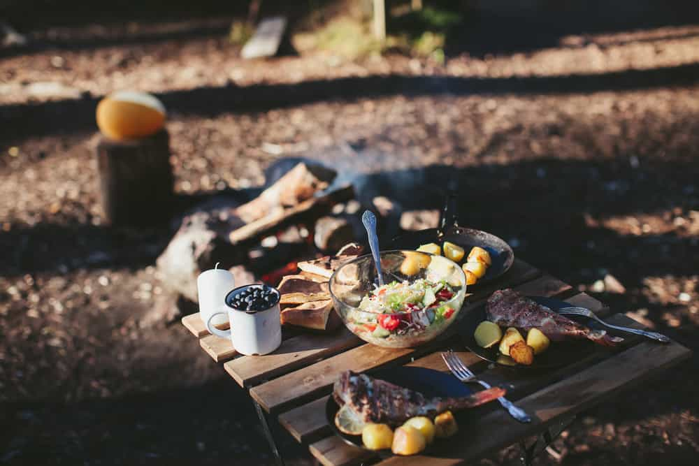 Camping food list with food sitting on a wooden table