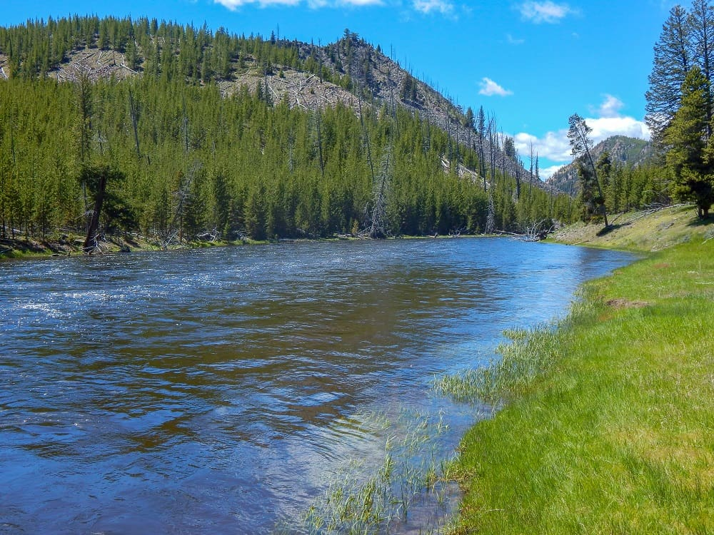 Family Camping Checklist to camp in the outdoors with mountains and a stream going through