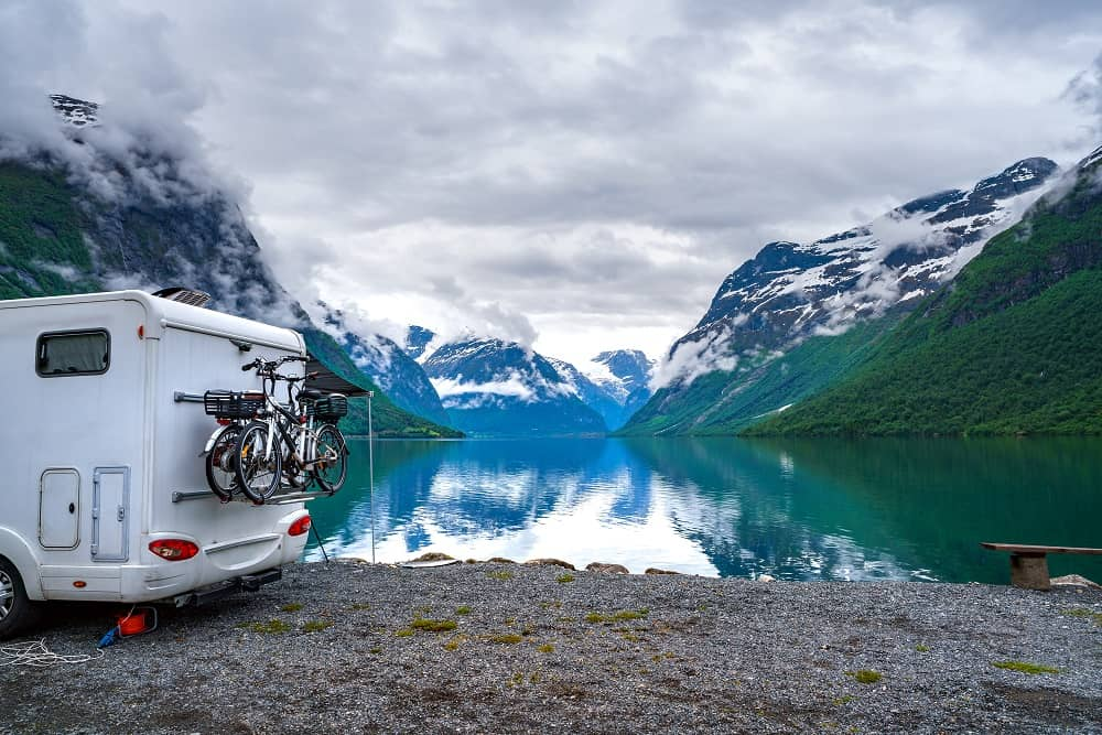 A rental RV parked in front of a lake surrounded by mountains with snow on them