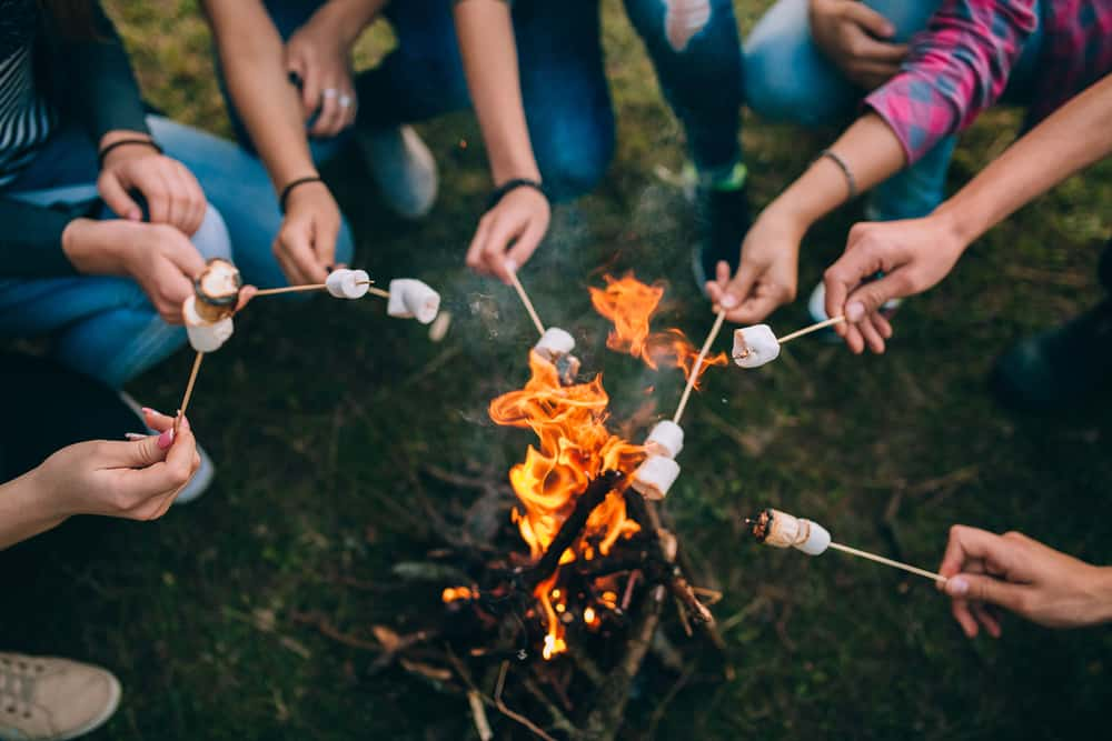 A group of people huddled over their fire using their family camping checklist
