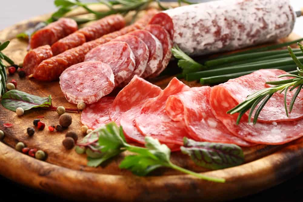 All kinds of meat, smoked sausage, salami on a platter, camping food without a fire