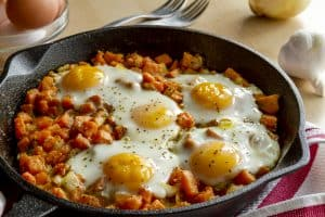 Camping cast iron skillet recipes with 5 eggs and hashbrowns in a skillet