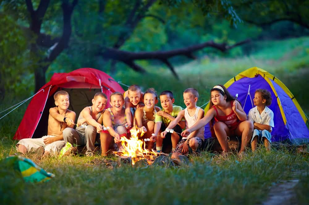 group of kids with camping food at fire