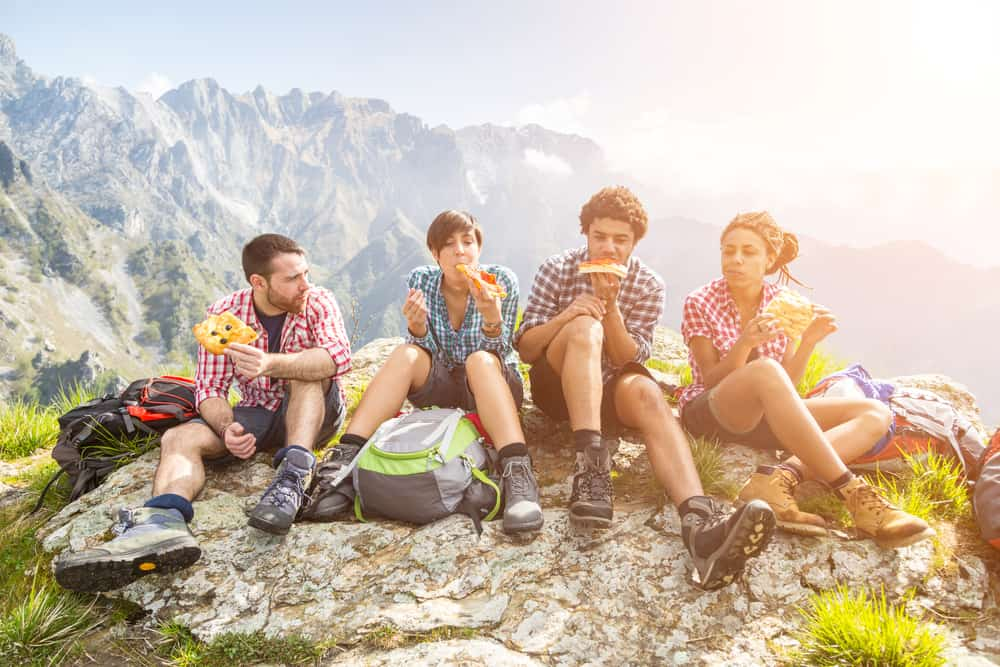 group eating camping food on hill top
