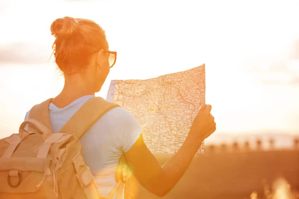 A young woman looking at a map while hiking