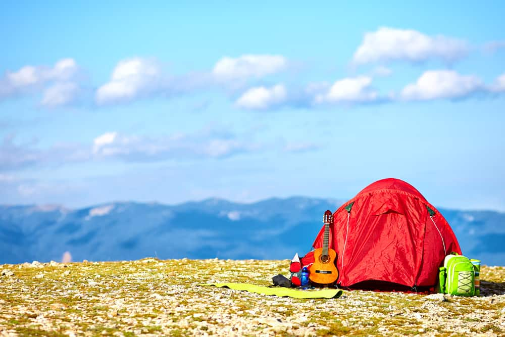 a red tent sitting atop a mountain