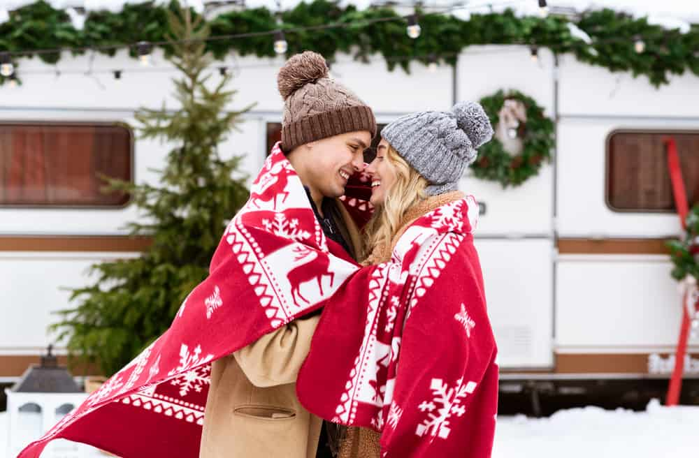 Man and woman kissing outside their Christmas decorated rv