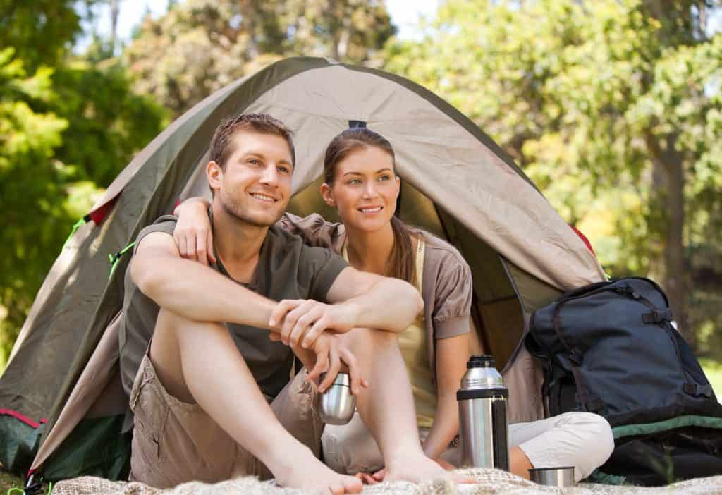 man and woman sitting outside a tent