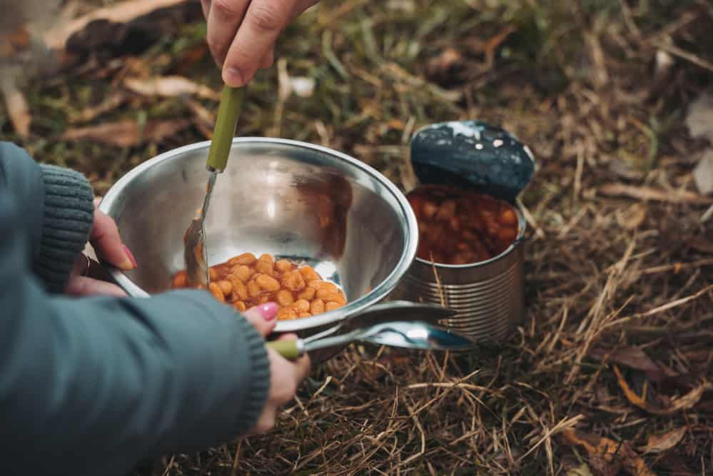 Cooking vegan beans over camping fire