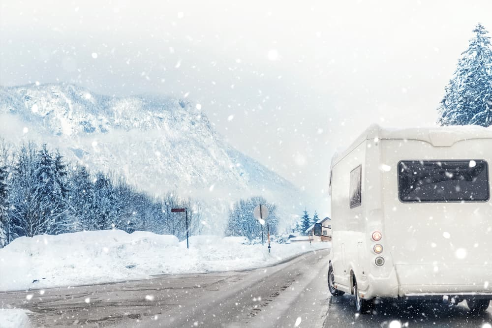 RV driving up snowy mountain