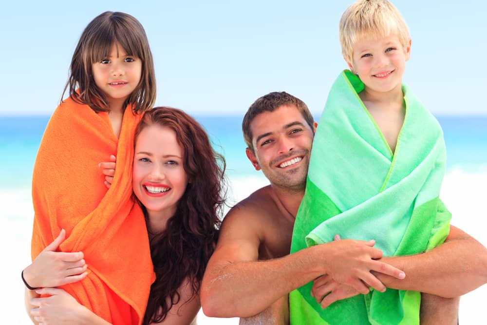 Family of 4 at beach with towels on