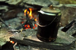 Coffee brewing over camping fire for breakfast