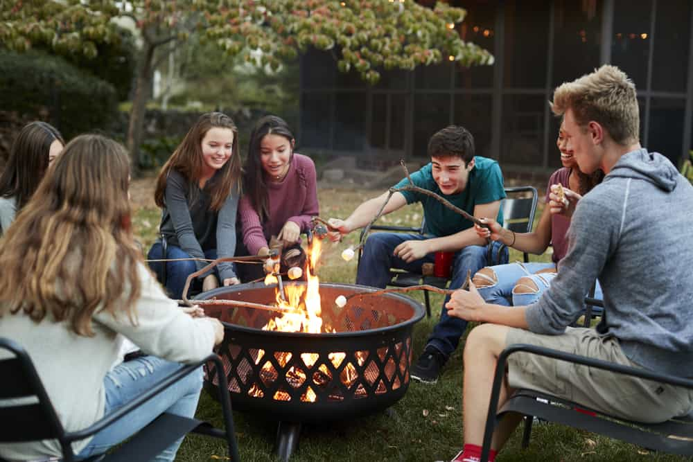 Teenage friends sit round a fire pit toasting marshmallows
