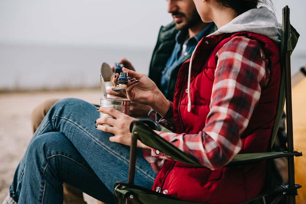 Couple at campground eating out of cans