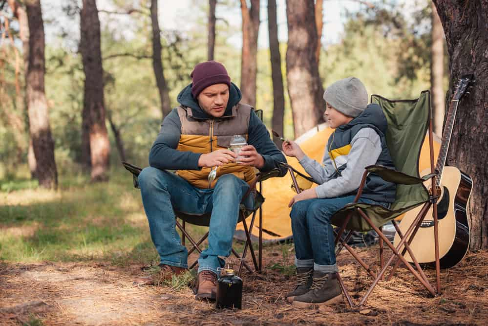 Father and young son eating outside tent