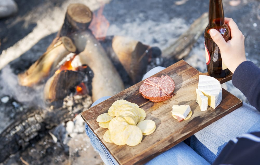 camping food on a wooden board, with cheese, salami and crackers with a beer in front of the fire